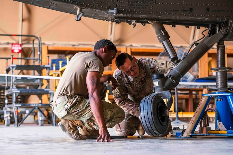 Two soldiers replace a tire on a helicopter.