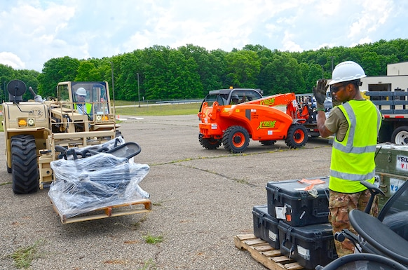 A man directs another man operating a forklift.
