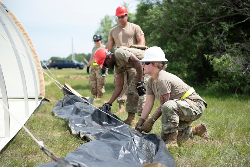 Troops put up a tent.