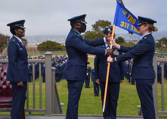 U.S. Air Force Lt. Col. William Taylor, incoming 311th Training Squadron commander, receives the guidon, a symbol of command, from Col. Stephanie Kelley, assistant commandant and commander of the 517th Training Group at the change of command ceremony at Soldier Field, Presidio of Monterey, California, June 4, 2021. Taylor comes to the Presidio of Monterey from the National Air and Space Intelligence Center, Ramstein Air Base, Germany. (Photo courtesy of Natela Cutter)