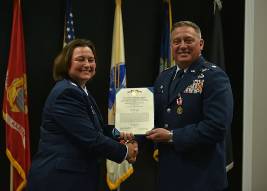 U.S. Air Force Col. Angelina Maguinness, 17th Training Group commander, presents Lt. Col. Herbert Millet III, 313th Training Squadron outgoing commander, the Meritorious Service Medal during the change of command ceremony at the Event Center on Goodfellow Air Force Base, Texas, June 11, 2021. Millet was decorated for his performance and dedication to the 313th TRS which led to the squadron winning the 2020 Air Education and Training Command Training Squadron of the Year. (U.S. Air Force photo by Senior Airman Ashley Thrash)
