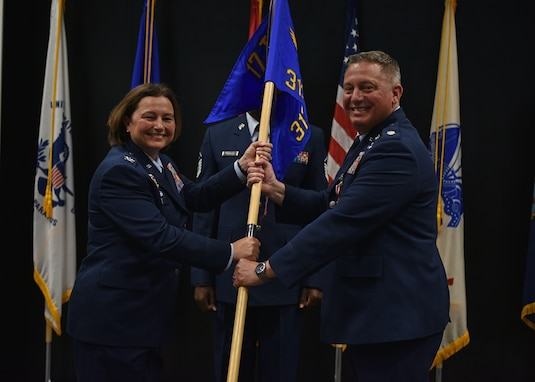 U.S. Air Force Col. Angelina Maguinness, 17th Training Group commander, takes the guidon from Lt. Col. Herbert Millet III , outgoing 313th Training Squadron commander, during the change of command ceremony at the Event Center on Goodfellow Air Force Base, Texas, June 11, 2021. Millet is leaving to attend senior development education at the Air War College at Maxwell Air Force Base, Alabama. (U.S. Air Force photo by Senior Airman Ashley Thrash)