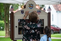 Nell Calloway, president of the Chennault Museum, adds a commemorative plaque to the new community book exchange box at Barksdale Air Force Base, June 8, 2021. Calloway is the granddaughter of Lt. Gen. Claire Chennault, to whom the book exchange box is dedicated.
