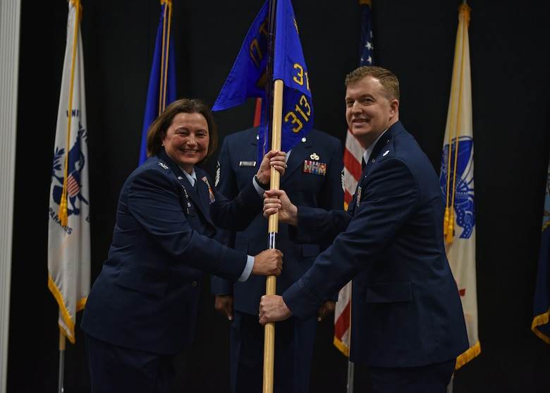 U.S. Air Force Col. Angelina Maguinness, 17th Training Group commander, passes the guidon to Lt. Col. Daniel Blackledge, incoming 313th Training Squadron commander, during the change of command ceremony at the Event Center on Goodfellow Air Force Base, Texas, June 11, 2021. Blackledge was previously the divison chief for the Joint Intelligence Operations Center at the U.S. Strategic Command in Nebraska. (U.S. Air Force photo by Senior Airman Ashley Thrash)