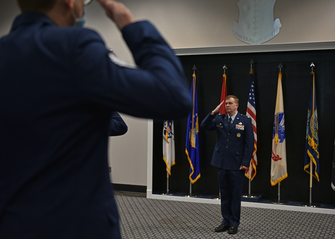 Members of the 313th Training Squadron salute U.S. Air Force Lt. Col. Daniel Blackledge, incoming 313th Training Squadron commander, during the change of command ceremony at the Event Center on Goodfellow Air Force Base, Texas, June 11, 2021. The salute represents the squadron welcoming their new commander. (U.S. Air Force photo by Senior Airman Ashley Thrash)