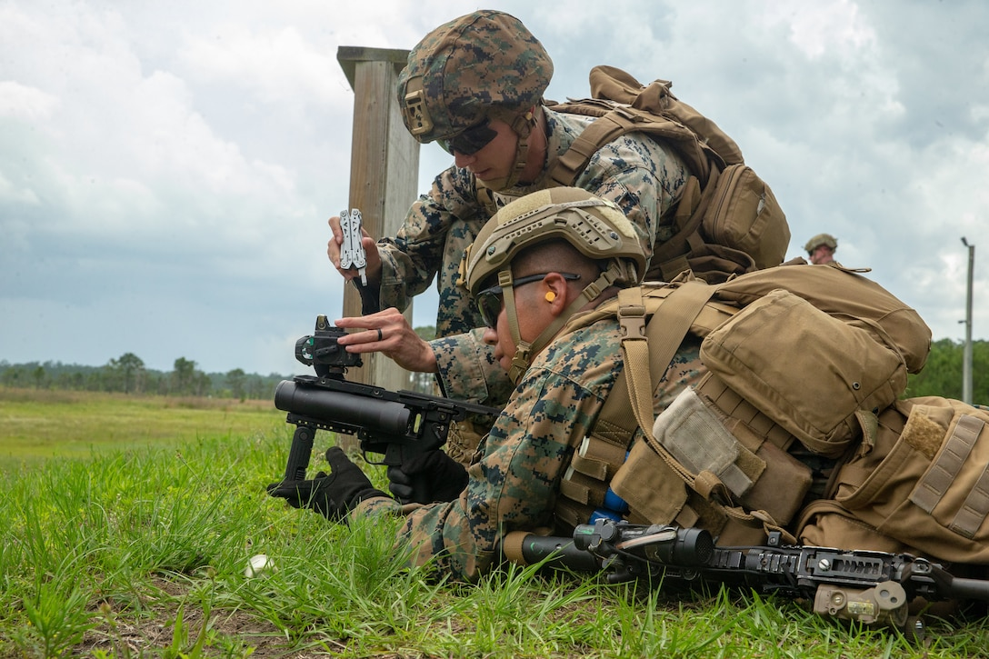 U.S. Marine Corps Cpl. Christian Wright and Lance Cpl. Brian Cifuentesperez, both infantry rifleman with 2d Battalion, 6th Marine Regiment, 2d Marine Division, adjust the optic of the M320 grenade launcher during a live-fire range on Camp Lejeune, N.C., June 10, 2021.