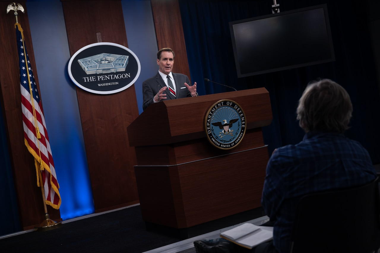 A man at a lectern speaks. A plaque on the wall behind him indicates that he is at the Pentagon.
