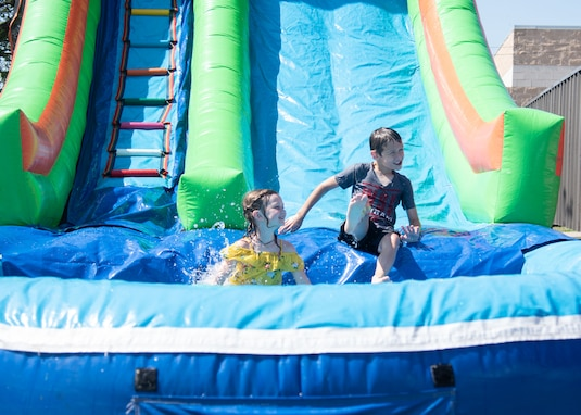 Dependents from Goodfellow Air Force Base play on an inflatable water slide during the 17th Force Support Squadron Block Party, on Goodfellow AFB, Texas. The event featured more than 10 different events inducing games and music. (U.S. Air Force photo by Staff Sgt. Tyrell Hall)
