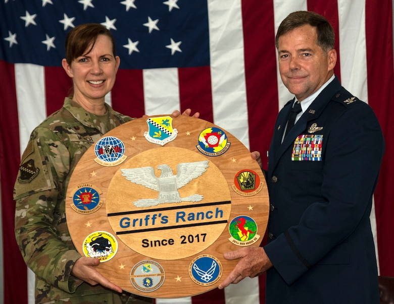 A woman wearing an Air Force camouflage uniform presents a plaque to a man wearing an Air Force Dress Blues.
