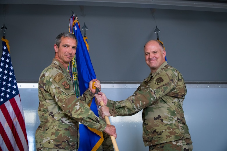 Maj. Gen. Bryan Radliff, 10th Air Force commander, passes the 926th Wing guidon to Col. Sean Rassas, the incoming 926th Wing commander during a change of command ceremony, June 13, 2021, at Nellis Air Force Base, Nevada. Rassis was previously assigned to the 944th Fighter Wing serving as the vice commander. (U.S. Air Force photo by Senior Airman Brett Clashman)