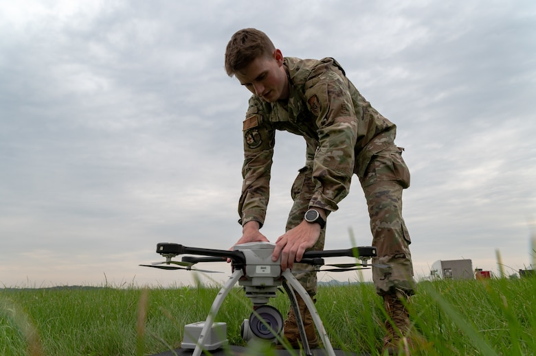 Staff Sgt. Nathan Powers, 51st Civil Engineer Squadron construction inspector technician, changes the battery on a small unmanned aircraft system at Osan Air Base, Republic of Korea, June 6, 2021. The rechargeable batteries of the Aeryon SkyRanger allow operators to perform continuous flights to inspect the airfield. (U.S. Air Force photo by Tech. Sgt. Nicholas Alder)
