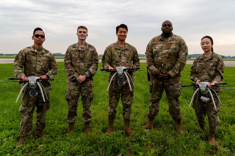 Small unmanned aircraft system operators from the 51st Civil Engineer Squadron, pose with their equipment at Osan Air Base, Republic of Korea, June 6, 2021. These operators conduct quarterly aerial assessments of the airfield, as part of the Rapid Airfield Damage Assessment System. (U.S. Air Force photo by Tech. Sgt. Nicholas Alder)