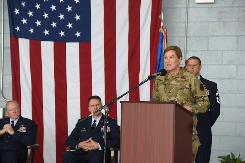 A woman in an air force uniform speaks at a podium.