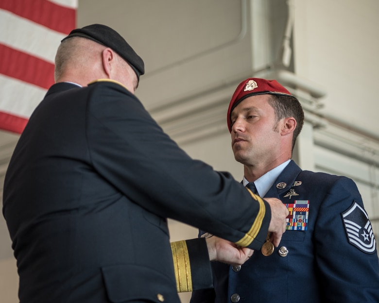 Brig. Gen. Hal Lamberton, left, the adjutant general for the Commonwealth of Kentucky, pins the Airman's Medal to the uniform of Master Sgt. Daniel Keller, a combat controller in the 123rd Special Tactics Squadron, during a ceremony at the Kentucky Air National Guard Base in Louisville, Ky., June 12, 2021. Keller earned the award for heroism in recognition of his actions to save human life following a traffic accident near Louisville in 2018.