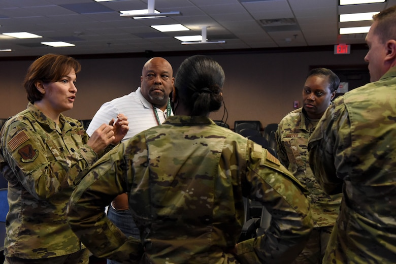 Five Airmen stand in a circle listening while one Airman speaks.