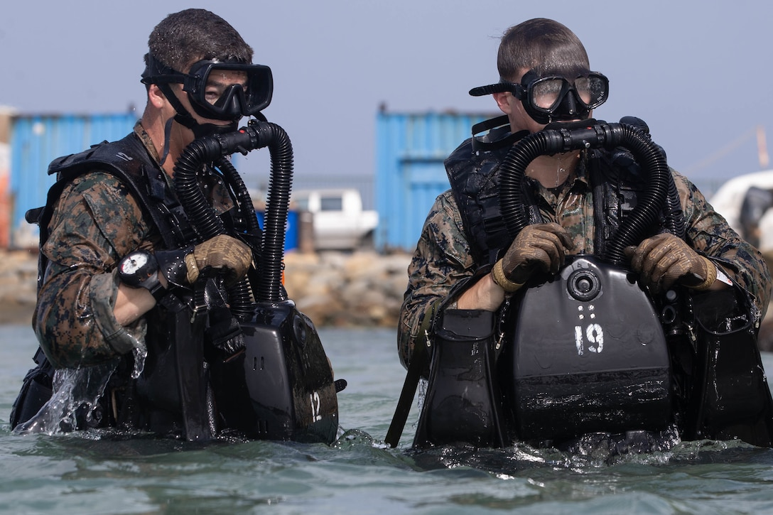 U.S. Marine Corps Sgt. Zachary Poster, a native from Charlston, S.C., right, and Lance Cpl. Jacob Derr, a native of Worcester, Mass. both reconnaissance Marines with 2d Reconnaissance Battalion (2d Recon), 2d Marine Division, emerge from the water after a buddy pair dive during Exercise Caribbean Coastal Warrior on Savaneta Kamp, Aruba, June 10, 2021.