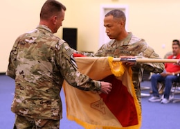 Command Sgt. Maj. Jose Hernandez (right) straightens out the Area Support Group-Qatar colors with his commander, Col. Stephen A. Fabiano at the June 10, 2021 end of mission ceremony at CampAsSayliyah, Qatar. The Army established ASG-Qatar in 1992, and for the last three decades, the military and civilian personnel deployed there supported military and humanitarian operations in the region. The ASG-Qatar merged with ASG-Jordan as part of the Army's ongoing realignment of assets and personnel. (U.S. Army photo by David Gomes)