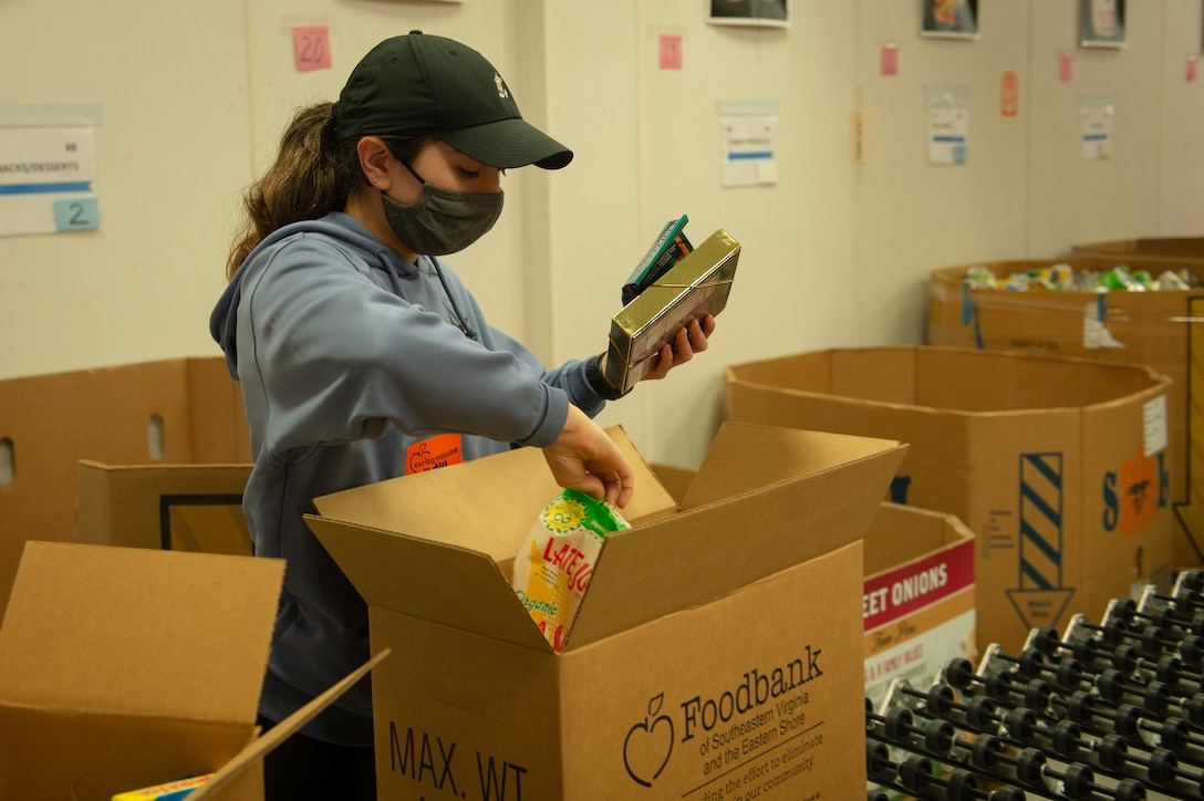 Navy Petty Officer 3rd Class Irely Garcia, assigned to the aircraft carrier USS John C. Stennis (CVN 74), puts donated food items into boxes at the Foodbank of Southeastern Virginia and the Eastern Shore, in Norfolk, Va., April 1, 2021. As part of President Joe Biden's strategy to stop the spread of COVID-19, Defense Logistics Agency Troop Support provided more than 400,000 adult and youth face masks to 16 local community centers, including foodbanks, in Philadelphia in May.