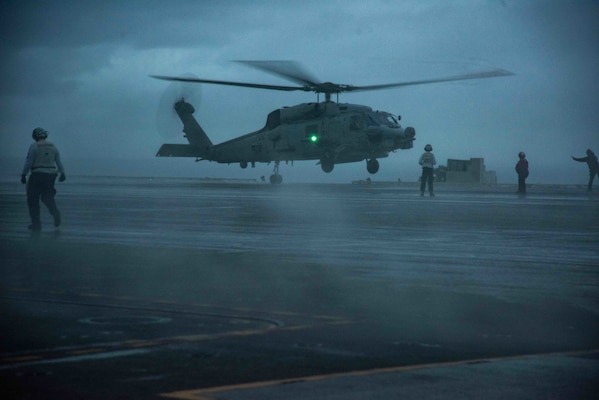 """An MH-60R Sea Hawk attached to the """"Saberhawks"""" of Helicopter Maritime Strike Squadron (HSM) 77 lands on the flight deck of the U.S. Navy's only forward-deployed aircraft carrier USS Ronald Reagan (CVN 76)."""