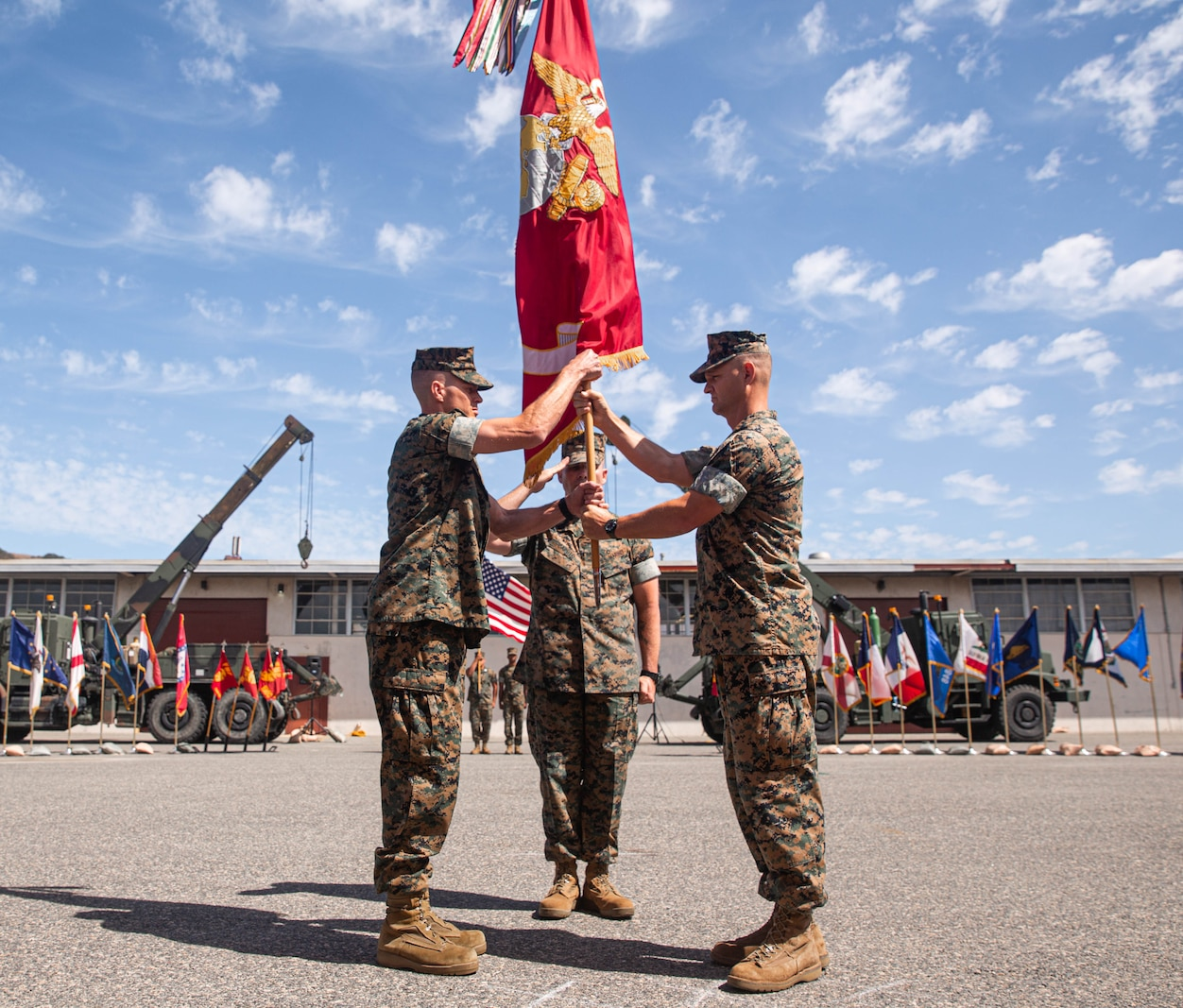 U.S. Marine Corps Lt. Col. Matt Hager, outgoing commanding officer, right, 1st Maintenance Battalion, and incoming commanding officer Lt. Col. Joseph R. Petkus, left, exchange the Battalion colors during the 1st Maint Bn change of command ceremony.