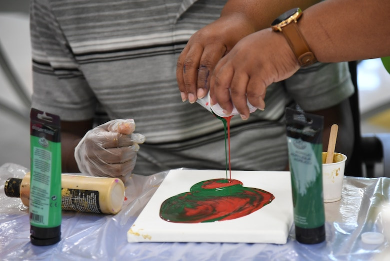 Shelena Gray, 81st Force Support Squadron teen coordinator, pours acrylic paints onto a canvas during the Keesler Youth Center fine arts camp at Keesler Air Force Base, Mississippi, June 10, 2021. The youth center offers a variety of camps throughout the summer for children of military personnel. (U.S. Air Force photo by Kemberly Groue)