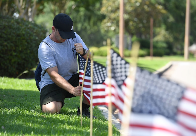 U.S. Air Force Airman 1st Class Michael Hanson, 338th Training Squadron student and member of the Air Force Sergeants Association Chapter 652, places a U.S. flag in the ground along Larcher Blvd. at Keesler Air Force Base, Mississippi, June 11, 2021. June 14 is Flag Day, a celebration of the history of the American flag and a time to remember proper etiquette for its display. Flag Day recognizes the adoption of the Stars and Stripes as the official flag of the United States 238 years ago on June 14, 1777, by the Continental Congress meeting in Philadelphia. (U.S. Air Force photo by Kemberly Groue)