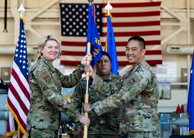 Two Airmen pass the guidon during a change of command ceremony.