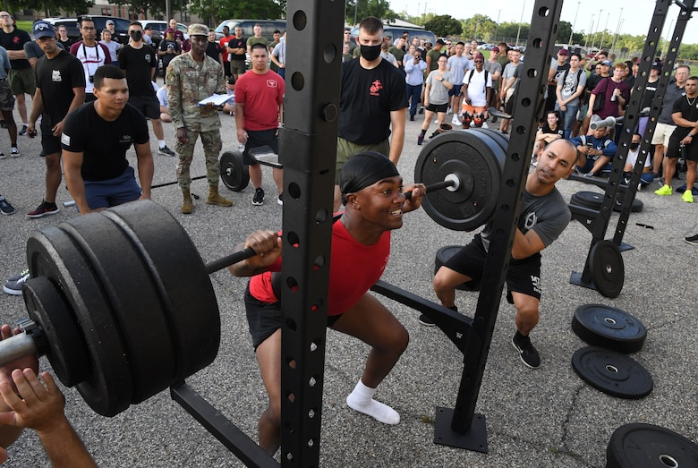 U.S. Air Force Airman Judah Officer, 336th Training Squadron student, participates in squats during the 81st Training Group Olympics at Keesler Air Force Base, Mississippi, June 11, 2021. The event also included competitions in long jump, track, shot put and discus. (U.S. Air Force photo by Kemberly Groue)