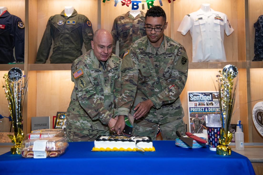 Military members cut Army birthday cake with sword