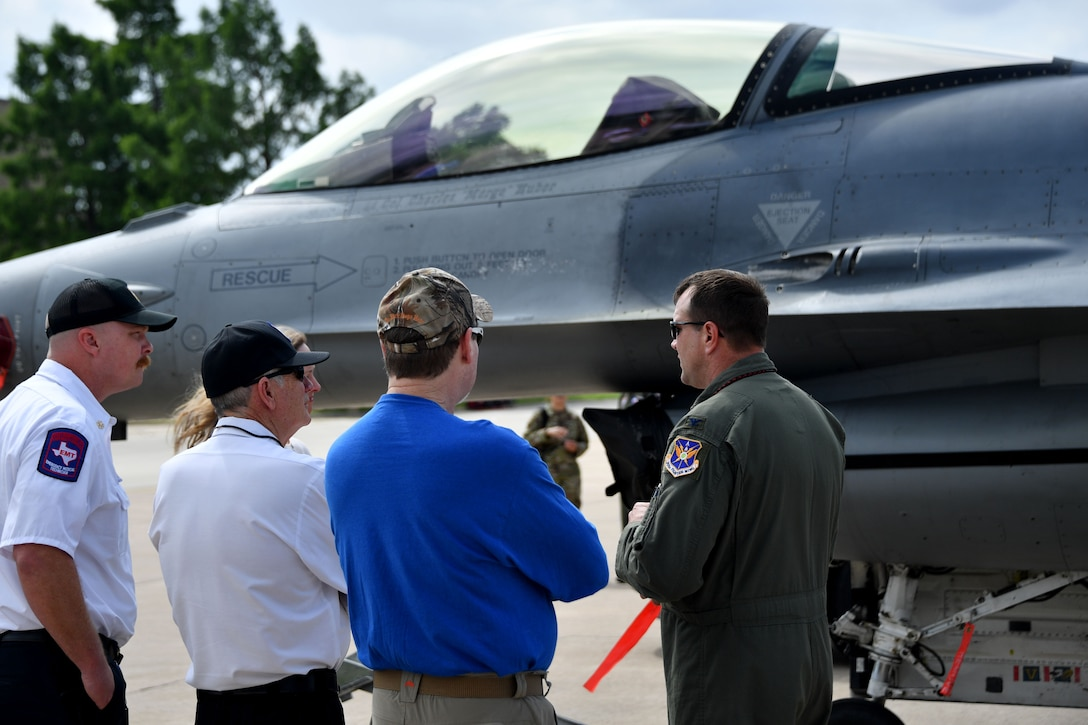 """(right) Col. Korey """"Axe"""" Amundson, 301st Fighter Wing vice commander, describes an F-16 Fighting Falcon for Dallas/Fort Worth civic leaders on June 11, 2021, at U.S. Naval Air Station Joint Reserve Base Fort Worth, Texas. The F-16 Fighting Falcon is a compact, multi-role fighter aircraft. It is highly maneuverable and has proven itself in air-to-air combat and air-to-surface attack. (U.S. Air Force photo by Staff Sgt. Randall Moose)"""