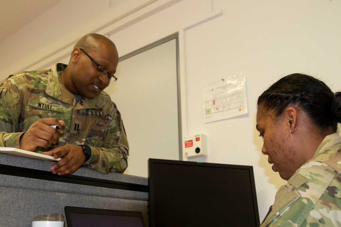 Cpt. Sibusiso Ntuli, left, health service systems management officer with 3rd Medical Command (Deployment Support) speaks with Cpt. Jessica Bradford, patient administration officer with the 3rd MC (DS) about future operations during a medical command post exercise, part of Defender Europe 21, on Daenner Kaserne in Kaiserslautern, Germany June 11, 2021. Defender Europe 21 is an annual large-scale U.S. Army Europe and Africa-led joint, multinational exercise designed to build readiness and interoperability between U.S., NATO and partner militaries.  (U.S. Army photo by Staff Sgt. Chris Jackson)