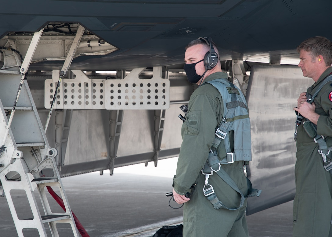 A U.S. Air Force Airman wearing a green flight suit approaches the crew ladder of a B-2 Spirit stealth bomber before a flight.