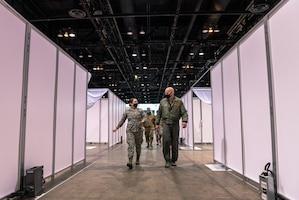 Airmen walking through McCormick Place alternative care facility.