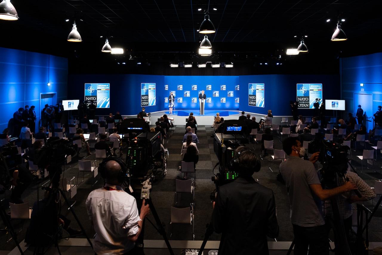 NATO leaders speak to an auditorium full of reporters.