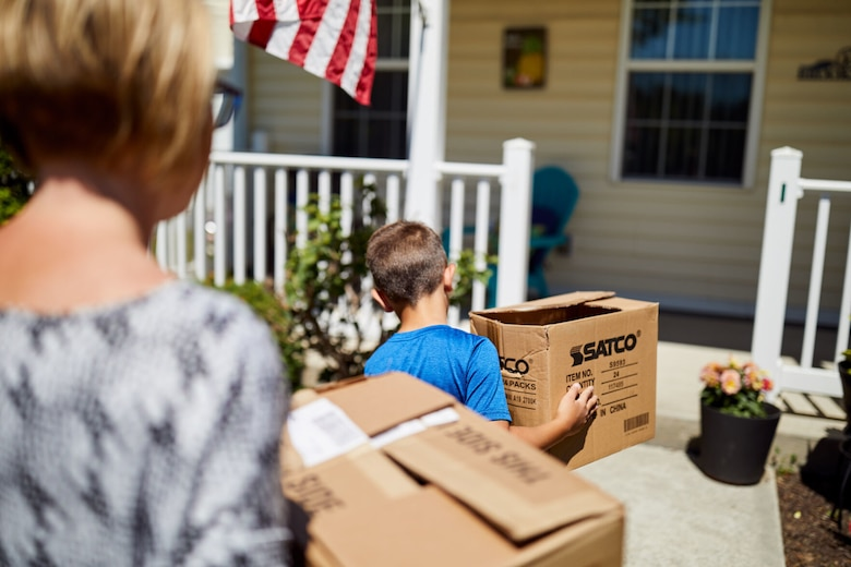 Woman and child carry moving boxes while walking into a house.