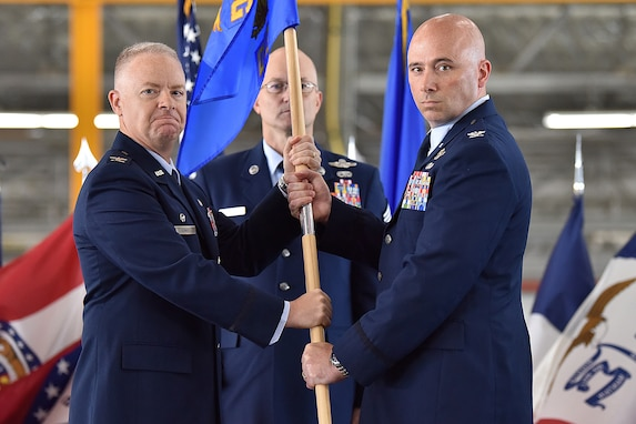 Col. John Ross, right, accepts command of the 316th Operations Group by taking the guidon from Col. Tyler Schaff, 316th Wing and installation commander, during a change of command ceremony, June 10, 2021, at Joint Base Andrews, Md. Chief Master Sgt. Harold Kruger, 316th Operations Group superintendent, looks on. Organizational flags were developed with color arrangements and symbols unique to each particular unit. (U.S. Air Force photo by Senior Airman Daniel Brosam)