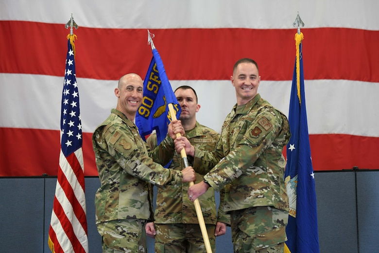 Col. Damian Schlussel, 90th Security Forces Group commander, passes the guidon to Maj. Justin May, 890th Missile Security Forces Squadron commander, during the 890 MSFS change of command ceremony June 14, 2021, in the Peacekeeper High Bay on F.E. Warren Air Force Base, Wyoming. The ceremony signified the transition of command from Maj. Robert Chance to May. (U.S. Air Force photo by Airman 1st Class Charles Munoz)