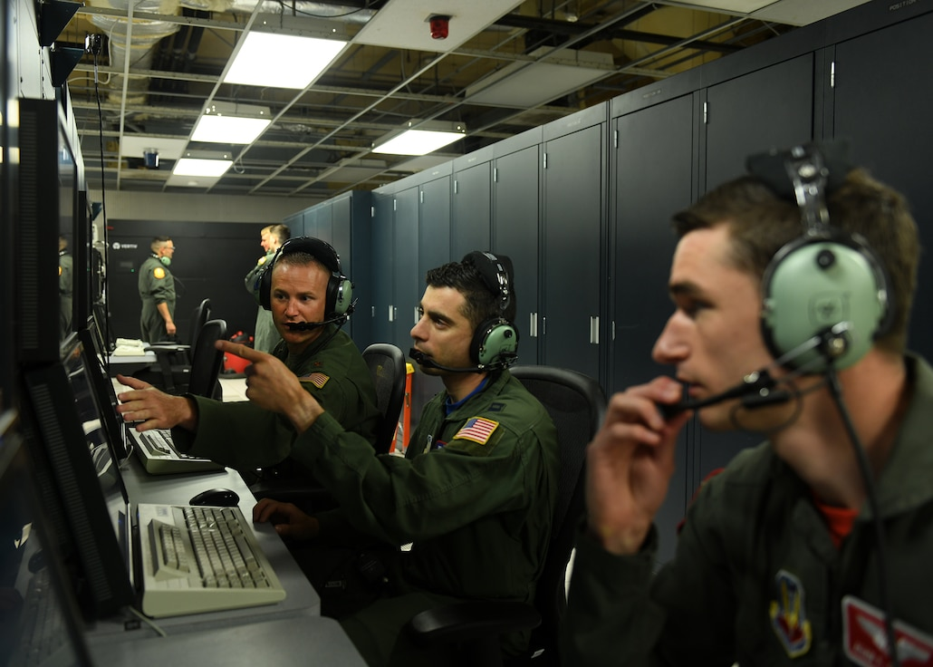 Three Airmen sit in front of a flight simulator terminal. Two men are pointing at computer screens.
