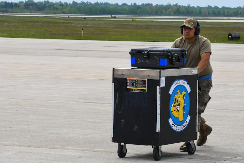 A photo of an airman pushing a tool box on a flight line