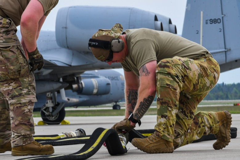 A photo of an airman prepping a hose for fueling