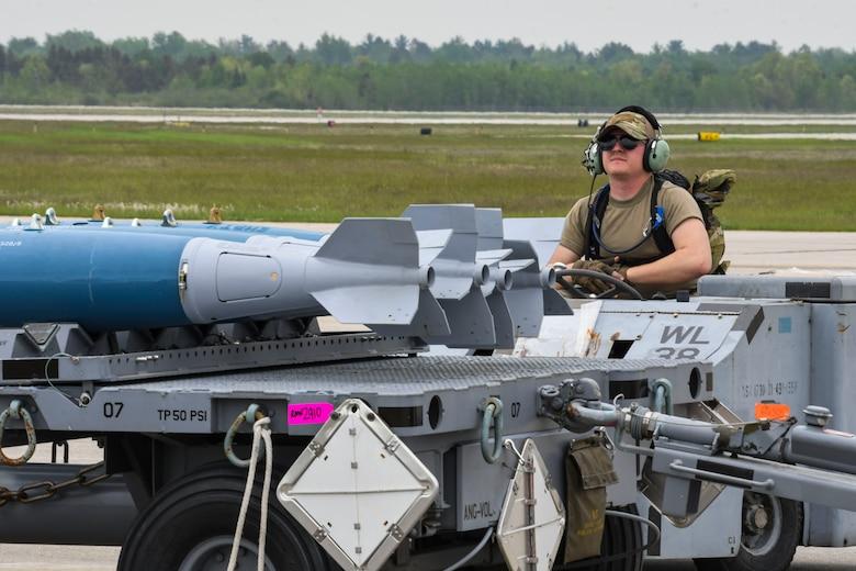 A photo of an airmen driving a bomb lift