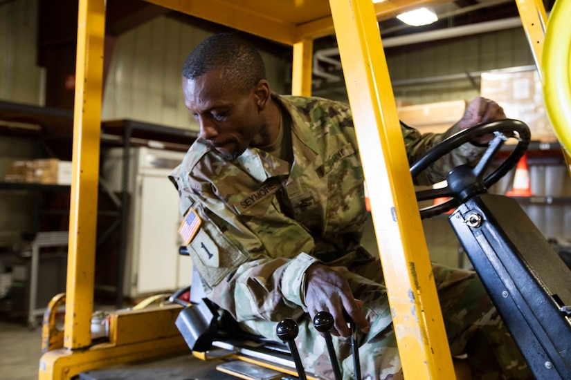 Alaska Army Guard Sgt. Shanun Seymore, United States Property and Fiscal Offices Supply Support Activity, operates a forklift to move freight for final processing at the USPFO warehouse on Joint Base Elmendorf-Richardson, June 7, 2021. (U.S. Army National Guard photo by Victoria Granado)