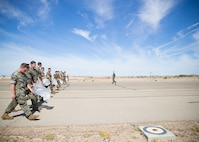 U.S. Marines conduct a Foreign Object Debris (FOD) walk along the runway at Marine Corps Air Station Yuma, Ariz., June 7, 2021. A FOD walk is conducted routinely to make sure runways are clear from debris that may damage aircraft using it. (U.S. Marine Corps Photo by Lance Cpl Matthew Romonoyske-Bean)