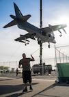 An AV-8B Harrier jet is lifted over a gate on Marine Corps Air Station Yuma, June 7, 2021. The Harrier is now a static display near the entrance of the Air Station. (U.S. Marine Corps photo by Lance Cpl. Carlos Kealy)