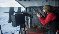 Gunner's Mate 2nd Class Lukas Hanson, from North Branch, Minnesota, aims a .50-caliber machine gun during a live-fire exercise on a weather deck aboard the Nimitz-class aircraft carrier USS Harry S. Truman (CVN 75) during Tailored Ship's Training Availability (TSTA) and Final Evaluation Problem (FEP).