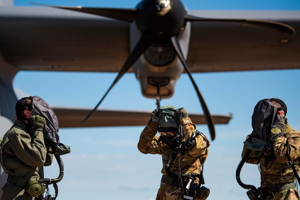 First Lt. Coltan Nading, 40th Airlift Squadron pilot, left, Capt. Miranda Mila, 40th AS pilot, center, and Senior Airman Noah Isom, 39th AS loadmaster, remove their gas masks next to a C-130J Super Hercules at Dyess Air Force Base, Texas, June 2, 2021. The aircrew demonstrated the operability of the new Uniform Integrated Protective Ensemble Air 2 Piece Under Garment chemical protective suit during simulated preflight and ground egress procedures.