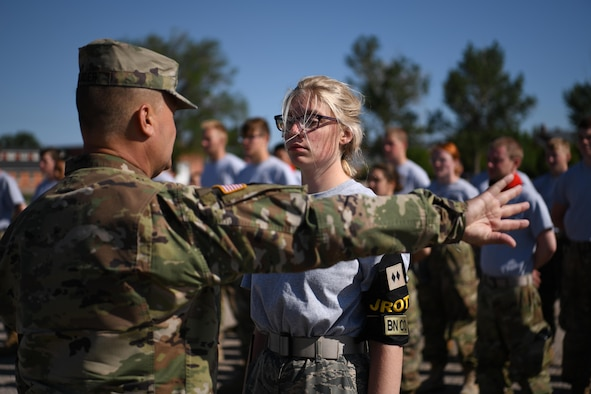 U.S. Army Sgt. Maj. Rodger Harder, instructor for Cheyenne Central High School Army Junior ROTC, instructs Willow Wilson, West Minister High School Air Force Junior ROTC cadet, at F.E. Warren Air Force Base, Wyoming, June 11, 2021. Junior ROTC cadets from five high schools throughout Colorado and Wyoming came to F.E. Warren AFB during Junior ROTC Cadet Leadership Camp. JCLC is a program designed to develop community involvement and leadership skills of high school students. (U.S. Air Force photo by Airman 1st Class Charles Munoz)