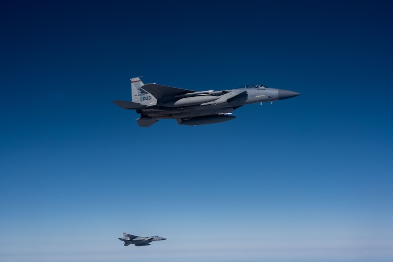 Two F-15 jet aircrafts is flying high in the sky.