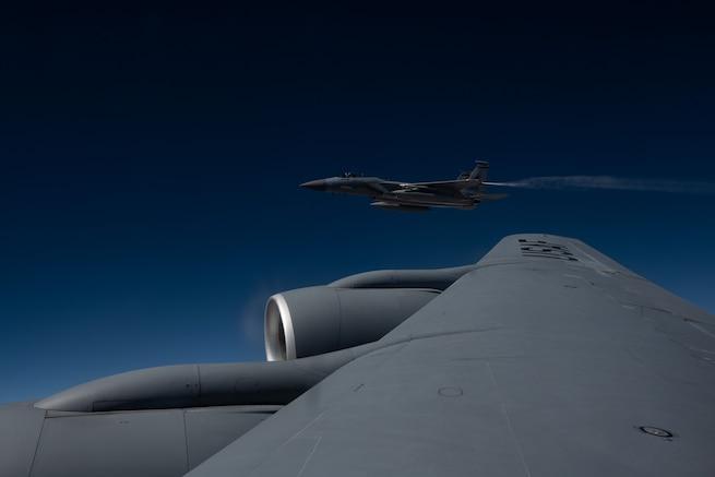 A F-15C jet flies next to KC-135 Startotanker.