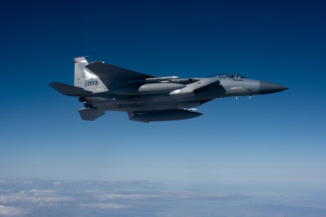 A F-15 jet aircraft is flying high in the sky.